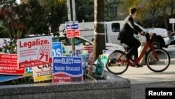 Áp phích ủng hộ cần sa, thứ hai từ trái sang, ở thủ đô Washington, ngày 4/11/2014. Tại thủ đô Washington, đề nghị đó sẽ cho phép người trên 21 tuổi được sở hữu và trồng cây cần sa.