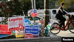 FILE - Various campaign signs crowd one corner of Washington, D.C., in November 2014.