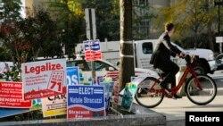 一名自行车骑士行经过首都华盛顿街头。左边第二张竞选标语主张允许年龄21岁以上的人拥有并种植大麻。