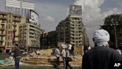 11月17日﹐一名男子在開羅解放廣場旁觀勞工修建基座,準備為2011年被安全部隊打死的示威者樹立紀念碑。