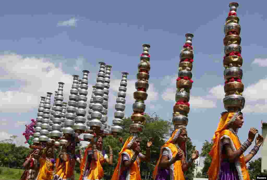 인도 서부 도시 아메다바드에서 힌두교 나브라트리 축제에 참가하는 여성 무용수들이 머리에 여러 개의 항아리를 엊은 채 춤을 추고 있다.