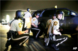 "FILE - Police take cover behind a vehicle during a protest in Ferguson, Missouri, Aug. 9, 2015. Some authorities blame a recent spike in homicides in select U.S. cities on the ""Ferguson effect."" Others disagree."