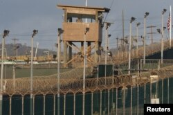 FILE - A military member observes from a watch tower at Camp Delta at the U.S. Detention Center in Guantanamo Bay, Cuba, in April 2010..