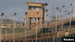FILE - A US military member mans one of the watch towers at Camp Delta at the US Detention Center in Guantanamo Bay, Cuba.
