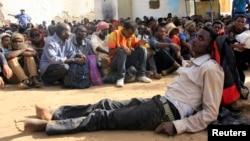 Imigran ilegal yang ditelantarkan para pedagang manusia menunggu di area padang pasir di dalam pangkalan militer di Kota Dongola setelah ditemukan oleh pasukan Sudan dan Libya, 3 Mei 2014.