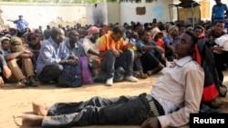 Les immigrants illégaux qui ont été abandonnés par des trafiquants dans une zone reculée du désert intérieur de la base militaire attendent dans la ville de Dongola, après avoir été Situé par les forces soudanaises et libyen, le 3 mai 2014.