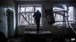 Seorang tentara pemberontak memeriksa sebuah rumah sakit di distrik Kalininsky, Donetsk yang terkena tembakan artileri pasukan Ukraina, Senin (19/1).
