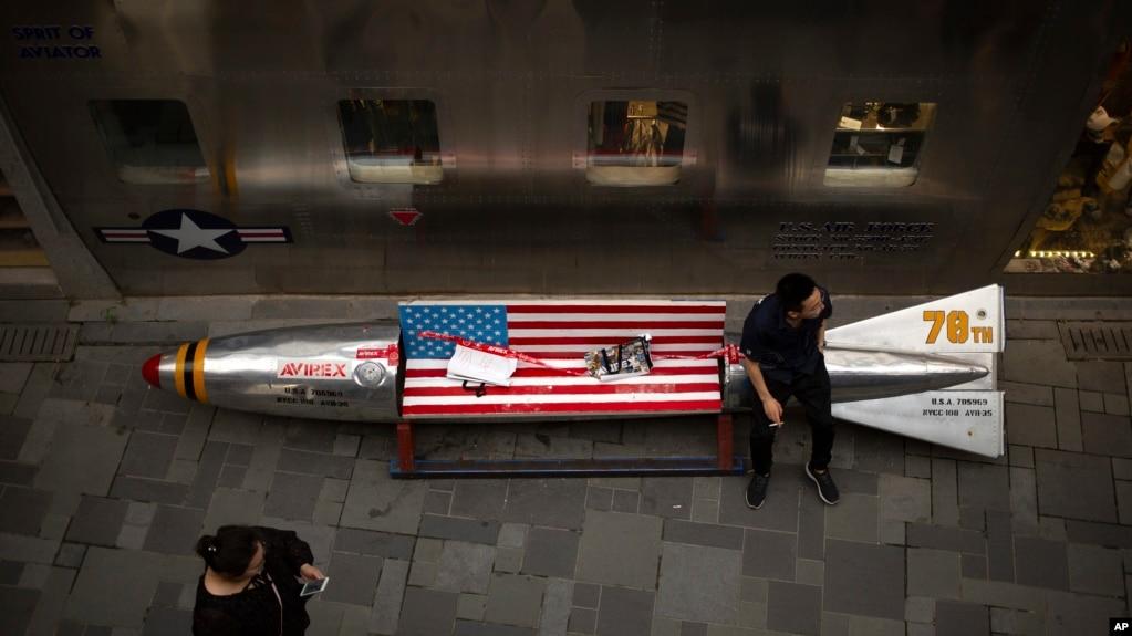 一名男子坐在位於北京的一家美國服裝店外的被裝飾成美國導彈的長椅上。 2018年7月5日。 (資料圖)