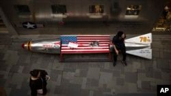 In this Thursday, July 5, 2018, photo, a man sits on a promotional gimmick in the form of a bomb and the U.S. flag outside a U.S. apparel shop at a shopping mall in Beijing, China.