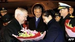 Một phụ nữ tặng hoa cho Bộ trưởng Gates khi ông đến phi trường quốc tế Bắc Kinh