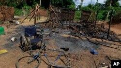 Le fauteuil roulant d'une victime, une femme dont le corps se trouve à proximité, au camp Dedjan, près de la rivière Cavally à l'ouest de la Côte d'Ivoire, le 26 mai 2011.