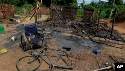 The wheelchair of Amelie Vlonhou, whose body lies nearby, sits beside a burned hut at the Dedjan campsite, near the banks of the Cavally River in western Ivory Coast, May 26, 2011.