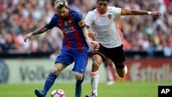 Enzo Perez de Valence, à droite, en duel avec Lionel Messi du FC Barcelone, à gauche, lors du match de football de la Liga espagnole entre Valence et le FC Barcelone au stade Mestalla à Valence, en Espagne, 22 octobre 2016.