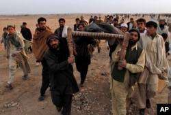FILE - Afghan people carry the body of a civilian killed in a suicide bombing on a small group of tribal elders and government workers in Khogyani district near Jalalabad, Nangarhar province east of Kabul, Afghanistan, Feb. 22, 2010.
