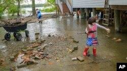 Devojčice čiste otpad sa poplavljene ulice na obali reke Misisipi u Nju Orleansu (Foto: AP/Matthew Hinton)