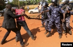 FILE - A supporter of Uganda's former Prime Minister Amama Mbabazi wrestles with the gun of a policeman, as riot police disperse a gathering in Jinja town in eastern Uganda, Sept. 10, 2015.