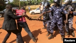 FILE - A supporter of Uganda's former Prime Minister Amama Mbabazi wrestles with the gun of a policeman, as riot police disperse a gathering in Jinja town in eastern Uganda, Sep. 10, 2015.