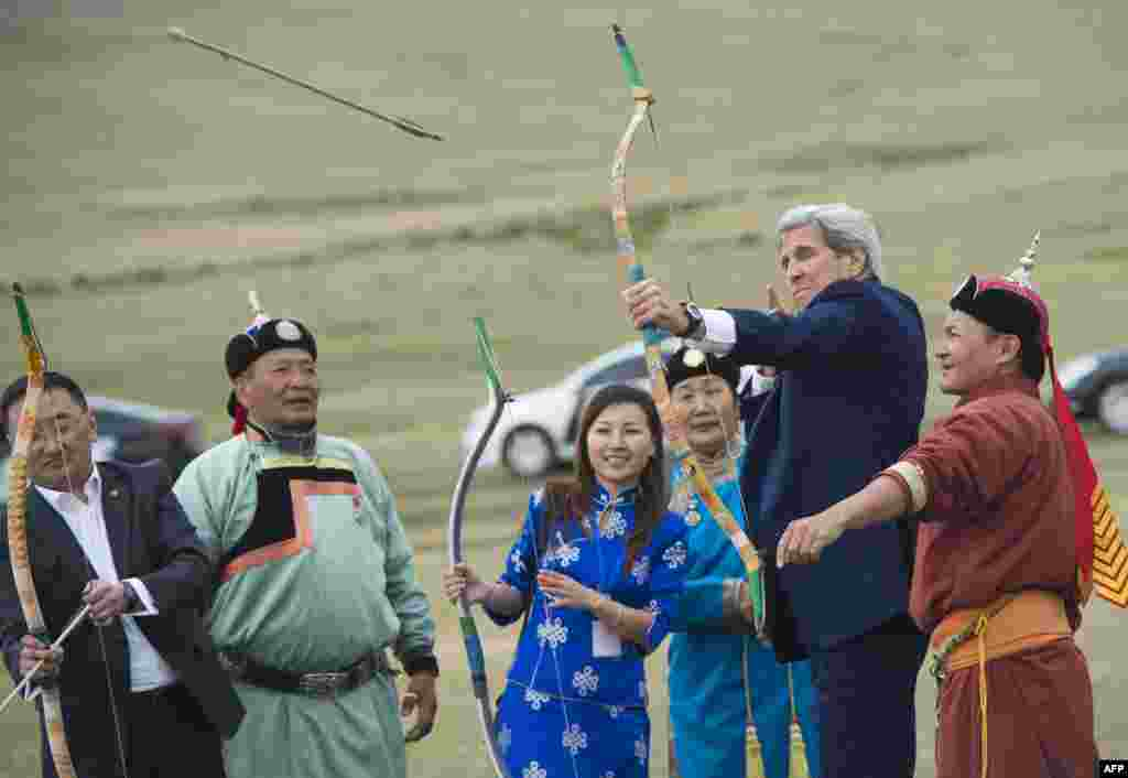 U.S. Secretary of State John Kerry shoots a bow and arrow as he participates in a Naadam ceremony, a competition which traditionally includes horse racing, Mongolian wrestling and archery, in Ulan Bator, Mongolia.