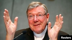 FILE - Cardinal George Pell talks during a news conference at the Vatican, July 9, 2014.