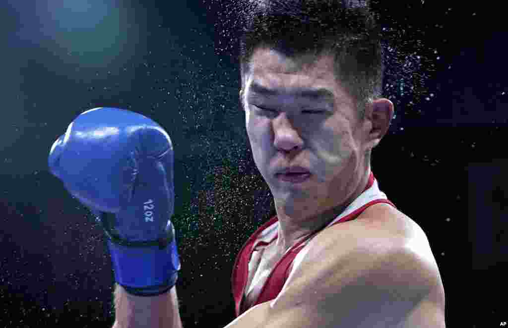 Russian Olympic Committee's Imam Khataev delivers a punch to Kazakhstan's Bekzad Nurdauletov during the men's light heavyweight 81-kg preliminaries boxing match at the 2020 Summer Olympics in Tokyo, Japan.