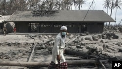 Man walks by destroyed farm school covered with volcanic ashes from eruption of Mount Merapi in Cangkringan, Indonesia, 14 Nov. 2010