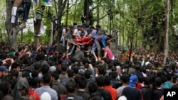 Kashmiri Muslim villagers carry the body of killed rebel commander Saddam Padder, during his funeral in Heff village 65 kilometers (41 miles) south of Srinagar, Indian-controlled Kashmir, May 6, 2018.