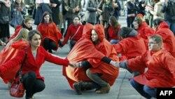 Румынские волонтеры изобразили красную ленточку - символ борьбы со СПИДом во время акции в Бухаресте. 29 ноября 2011г.