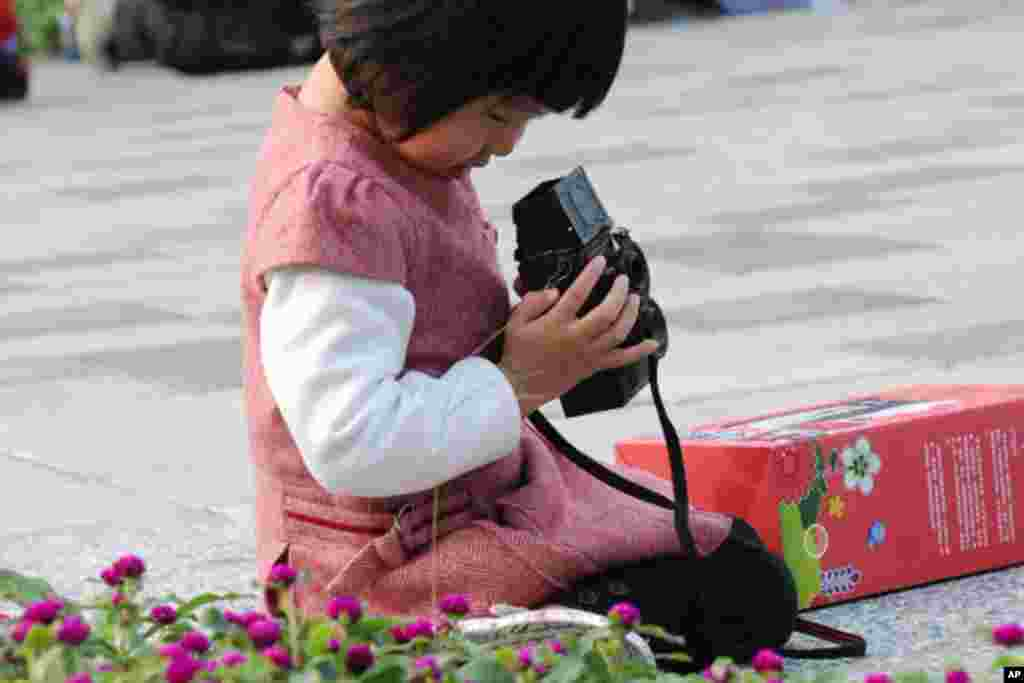 小女孩在花卉旁玩照相机