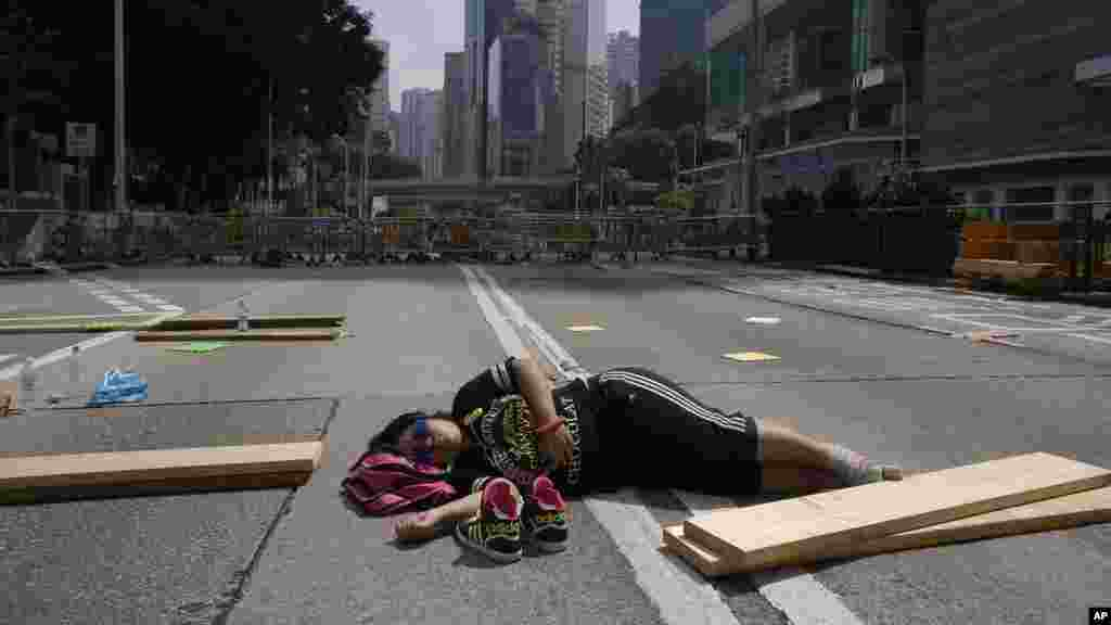 A lone pro-democracy student protester sleeps in the middle of an occupied road in Hong Kong, Oct. 5, 2014.
