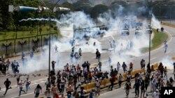 Pasukan keamanan menembakkan gas air mata ke arah demonstran anti pemerintah di Caracas, Venezuela, Rabu (19/4).