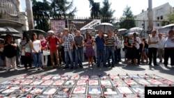 Para demonstran berdiri di belakang korban yang teas dalam kecelakaan kerja sebelumnya, memprotes kecelakaan kerja pada hari Sabtu di lokasi pekerjaan gedung, Istanbul, Minggu, 7 September 2014.