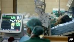 Hình minh họa - Một nhân viên bệnh viện theo dõi các dấu hiệu sinh tồn của bệnh nhân nghi nhiễm cúm gia cầm.