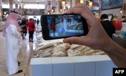 FILE - A gamer uses the Pokemon Go application on his mobile in the main fish market in Kuwait City, July 14, 2016.