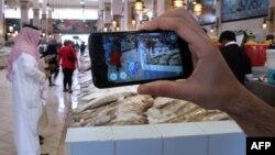 Seseorang menggunakan aplikasi game Pokemon di sebuah pasar ikan di Kuwait City, Kuwait (14/7). (AFP/Yasser al-Zayyat)