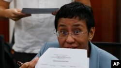 Maria Ressa, the award-winning head of a Philippine online news site Rappler that has aggressively covered President Rodrigo Duterte's policies, shows an arrest form after being arrested by National Bureau of Investigation agents in a libel case, Feb. 13, 2019.