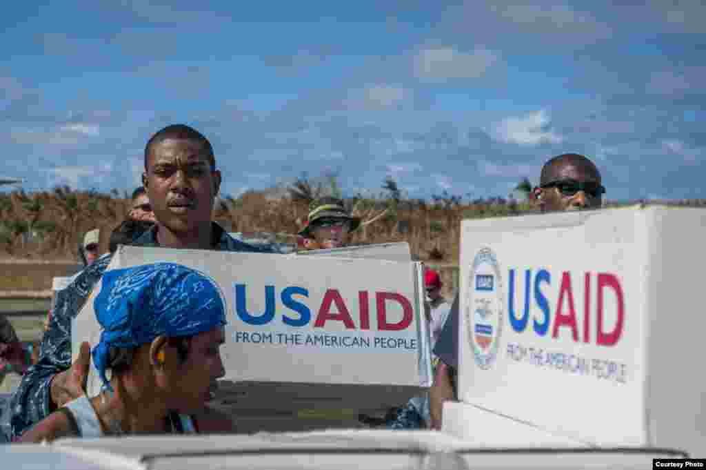 Hospital Corpsman Quinton Dotson, from the U.S. Navy's forward-deployed aircraft carrier USS George Washington (CVN 73), from Reno, Nev., left, and other U.S. military personnel and Philippine citizens unload relief supplies in support of Operation Damaya