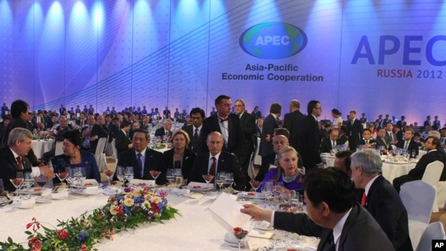 Russian President Vladimir Putin, center, and U.S. Secretary of State Hillary Clinton, fourth right, attend a reception at the APEC summit in Vladivostok, Sept. 8, 2012.