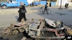 12月22号,一名妇女走过巴格达北部一个炸弹坑。