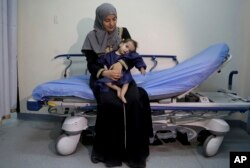 In this Monday, March 5, 2018 photo, Syrian refugee Sara al-Matoura holds her one-year-old daughter, Eman, before her surgery at a hospital in Amman, Jordan.