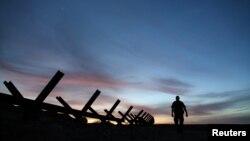 Arhiva - Agent granične patrole hoda pored granične barijere koja razdvaja SAD i Meksiko, u blizini Kaleksika, Kalifornija, 8. februara 2017.