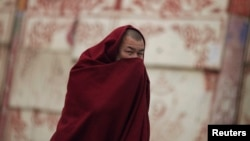 Tibetan monk covers his face as he walks along a street near Labrang Monastery, Xiahe county, Gansu Province, Feb. 11, 2013.