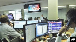 Brokers at a Lisbon trade room follow on video screens the Portuguese government bonds' auction, 12 Jan 2011