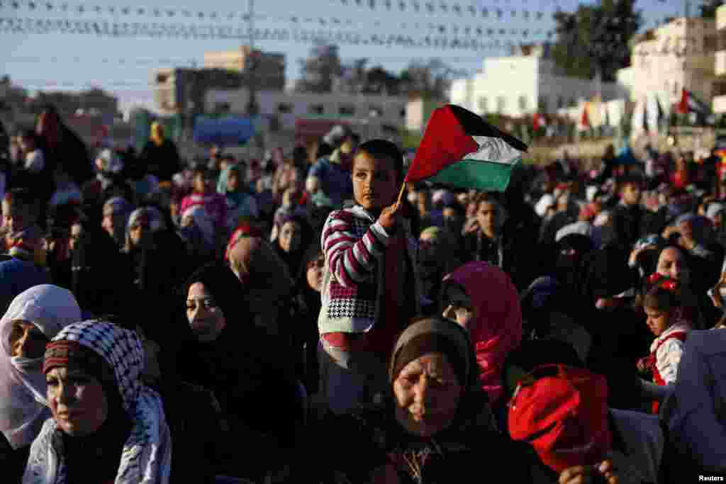 A boy waves a Palestinian flag during a mass wedding for 250 couples in Rafah in the southern Gaza Strip December 19.