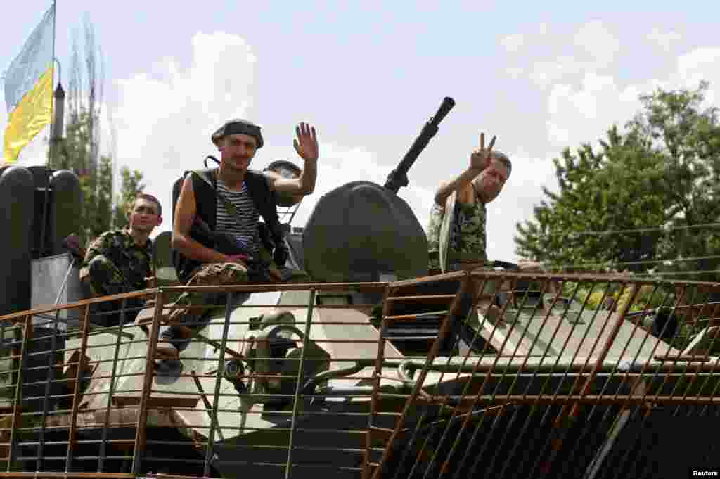 Ukrainian servicemen wave as they drive past in an armoured vehicle in the eastern Ukrainian town of Kramatorsk, Aug. 5, 2014.