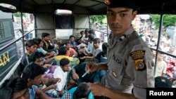An Indonesian policeman guards ethnic Rohingya refugees from Myanmar as they wait inside a police truck for identification by immigration personnel in Lhokseumawe, Feb. 27, 2013.