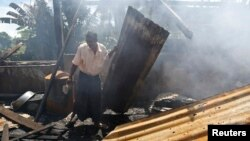 A man clears debris from the mosque that was burnt down in recent violence at Thapyuchai village, outside of Thandwe, in the Rakhine state, Oct. 3, 2013.