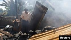 塔蒲寨村日前发生族群骚乱,村里的清真寺被焚毁。这是一名男子在清理废墟。