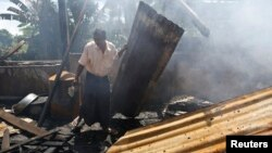 Seorang warga muslim Rohingya membersihkan reruntuhan Masjid di desa Thapyuchai, pinggiran kota Thandwe, yang dibakar warga Budha (3/10).