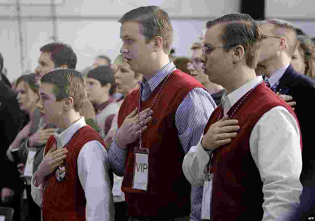Brothers, from left, Laine, Logan and Luke Hicks, recite the Pledge of Allegiance before Republican presidential candidate Rick Santorum speaks at a Kalamazoo, Michigan rally on February 27, 2012. (AP)