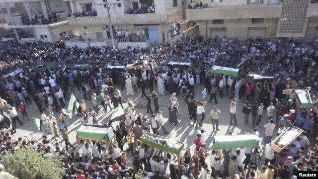 Syrian residents carry the bodies of people whom protesters say were killed by forces loyal to Syria's President Bashar al-Assad, during their funeral in Dara'a June 9, 2012.